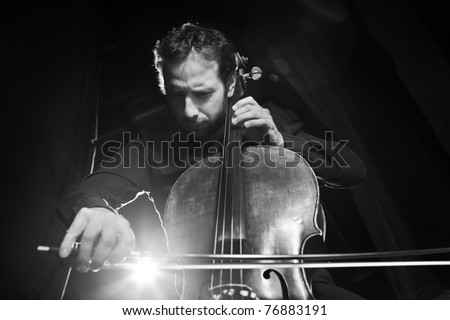 Dramatic portrait of cellist playing classical music on cello on black background. Copyspace. - stock photo