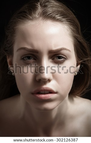 dramatic portrait of serious young woman on black background
