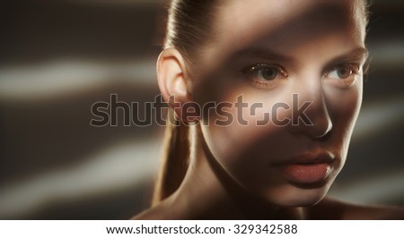 Dramatic portrait of woman with lights and shadows on her face.
