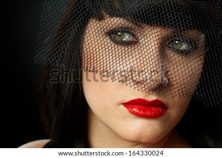 Dramatic portrait of young widow wearing elegant black clothes and in veil. - stock photo