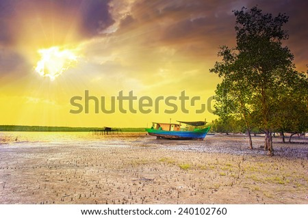 dramatic ray of sunrise and cloud at fishing village - stock photo