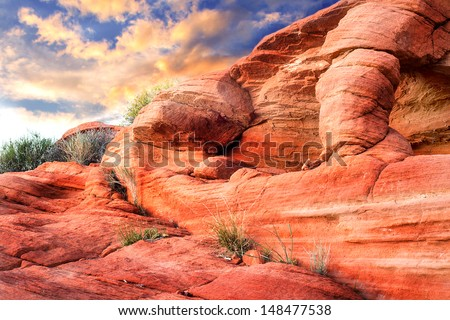 Dramatic Red rock sculpture with sunset in background - stock photo
