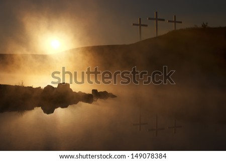 Dramatic religious photo illustration of Easter Sunday Morning reflecting a prayerful moment as a warm sun rises over a foggy lake, and three crosses on a hill reflect in the water below. - stock photo