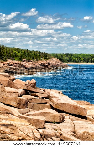 Dramatic rocky coastline at Acadia National Park, Maine, USA. Popular Sand Beach is in the distance. - stock photo