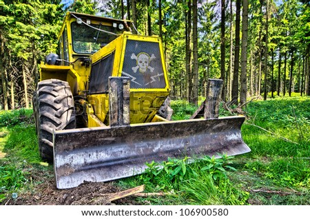 Dramatic scene in the forest with terrible bulldozer - stock photo