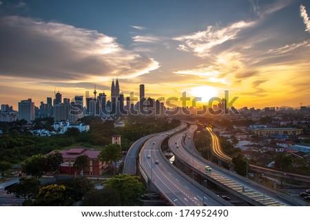 Dramatic scenery of elevated highway heading towards Kuala Lumpur city centre during sunset - stock photo