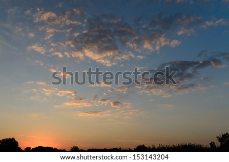Dramatic scenic nature image with horizon line under a cloudy sky at sunset - stock photo