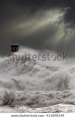 Dramatic seascape with big stormy waves over lighthouse in a dark cloudy winter noon with sunbeams. Enhanced sky. Focus on the foreground waves.