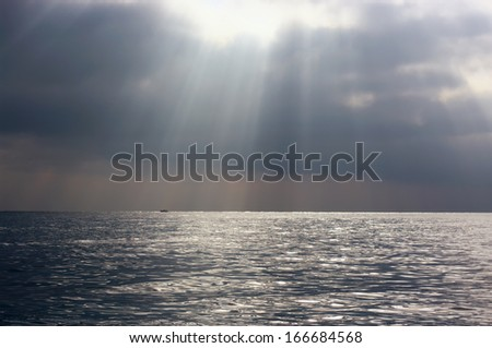 Dramatic seascape with clouds and sunbeams. - stock photo