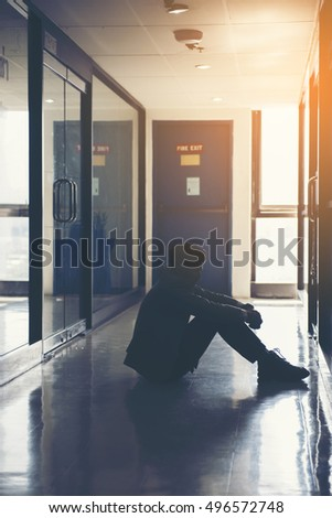 Dramatic Silhouette of businessman sitting alone,Sad and Serious Man sitting hug his knee front of close office.With his reflecing shodow..Split tone instragram like.With hot light process.