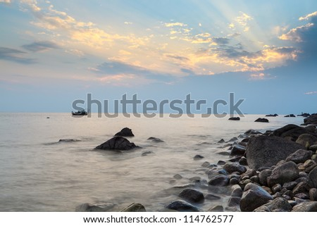 dramatic sky and pebble beach at sunset