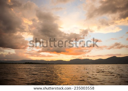 Dramatic sky obove the lake  sunset with red, yellow and orange colors.  - stock photo