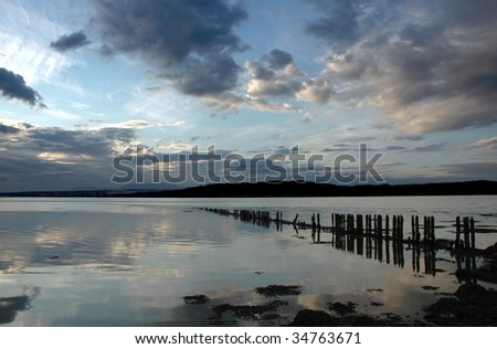 Dramatic sky over a Loch at dusk - stock photo