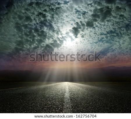 Dramatic sky over an asphalt road - stock photo