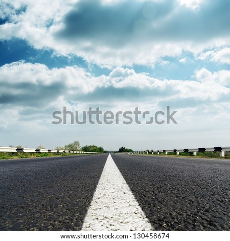 dramatic sky over asphalt road - stock photo