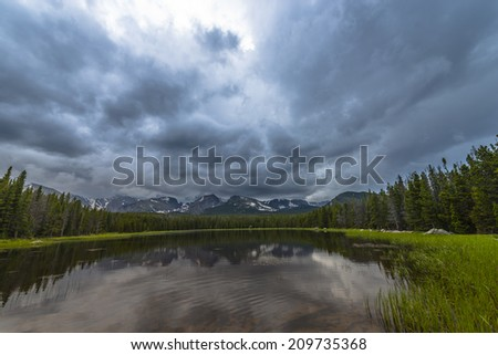 Dramatic sky over beautiful Bierstadt Lake with view of The Continental Divide Taylor, Hallett Peak, Andrews, Tyndoll Glacier, Flattop Mountain Rockies Colorado  - stock photo