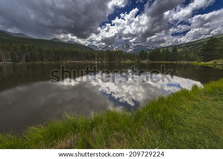 Dramatic sky over beautiful Sprague Lake with view of the Continental Divide-Half, Thatchtop, Flattop  Mountain, Taylor, Otis, Hallett Peak, Colorado  - stock photo