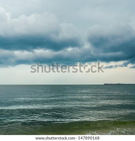 dramatic sky over dark sea - stock photo