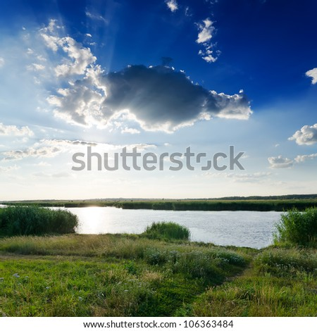 dramatic sky over river - stock photo