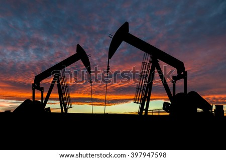 Dramatic sky over two pumpjacks in rural Alberta, Canada. These jacks can extract between 5 to 40 liters of crude oil and water emulsion at each stroke. - stock photo