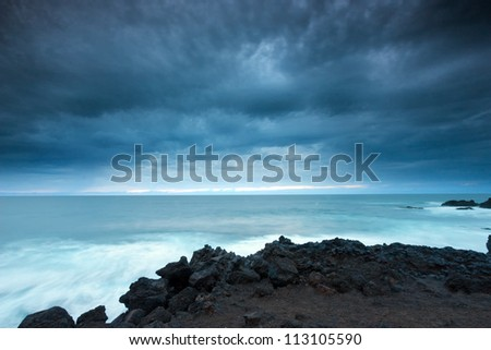 Dramatic sky over volcanic coast at dusk . Lanzarote, Canary Islands, Spain . - stock photo
