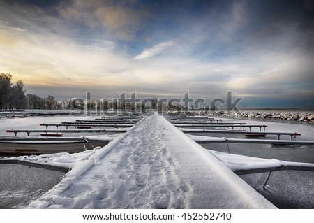 Dramatic sky over winter lake and long pier. - stock photo