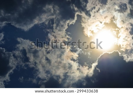 Dramatic sky with bright sun and dark clouds - real photo - stock photo
