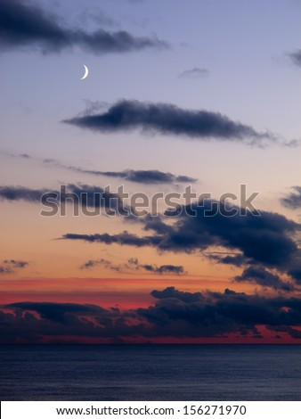 Dramatic sky with dark clouds, red sky and the Moon in clear sky across English Channel. - stock photo