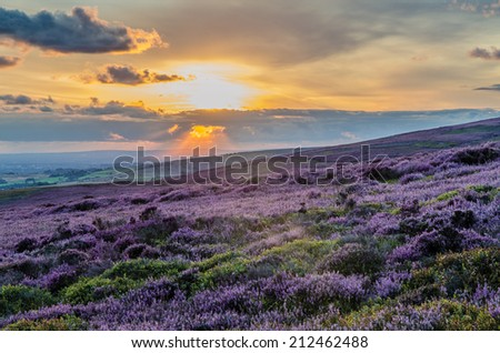 Dramatic sky with god rays illuminating Manchester below - stock photo