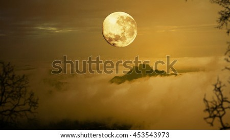 Dramatic sky with tree, full moon, fog and clouds over mountain, Orange warm tone.
