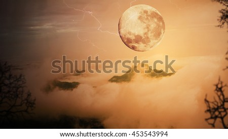 Dramatic sky with tree, full moon, fog and clouds over mountain, Orange warm tone. - stock photo