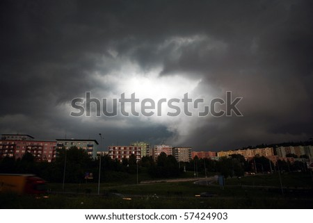 Dramatic stormy clouds over row of houses - stock photo