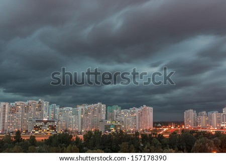 Dramatic stormy dark cloudy sky over row of typical residential district