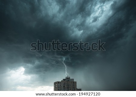Dramatic stormy sky with lightning over the residential building - stock photo
