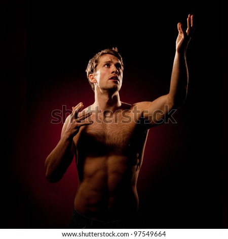 Dramatic studio shot of young handsome strong man looking to the light reaching for something