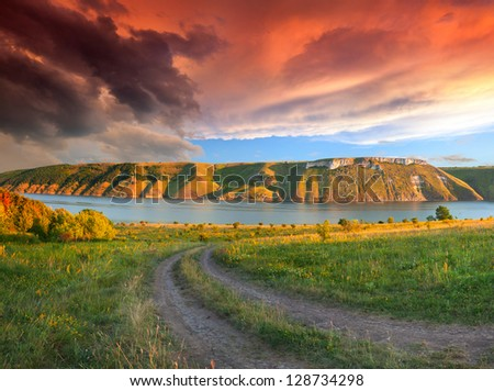 Dramatic summer landscape with the river in the mountains. Sunset - stock photo