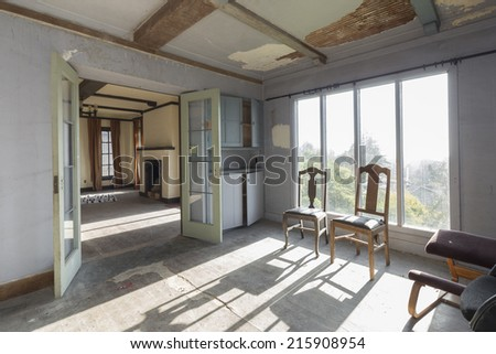 Dramatic sunlight in living room with french doors and chairs.  - stock photo