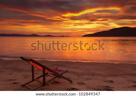 Dramatic sunrise in Phuket, Thailand, with resting chair on foreground