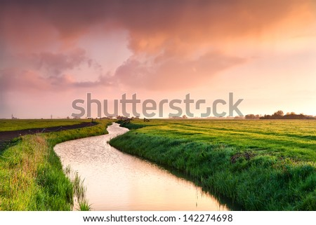 dramatic sunrise over canal in Dutch farmland, Groningen - stock photo