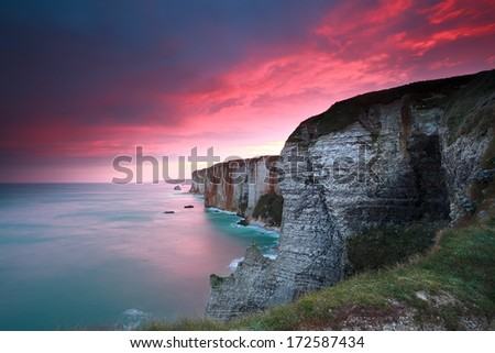 dramatic sunrise over cliffs in Atlantic ocean, Etretat, France