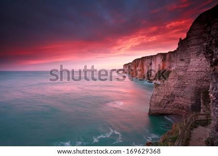 dramatic sunrise over ocean and cliffs, Etretat, France - stock photo