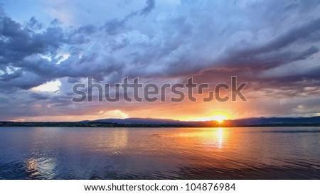 Dramatic sunrise over quiet lake - stock photo