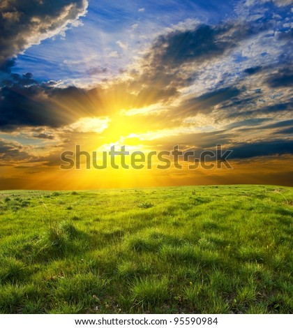 dramatic sunset among a green fields