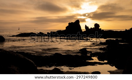 Dramatic sunset and rocky coastline at Newport Beach, California