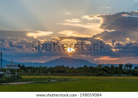 Dramatic sunset in a field. - stock photo