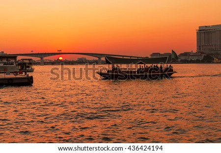 Dramatic sunset on river with bridge and boat in Chaophraya river, Bangkok, Thailand - stock photo