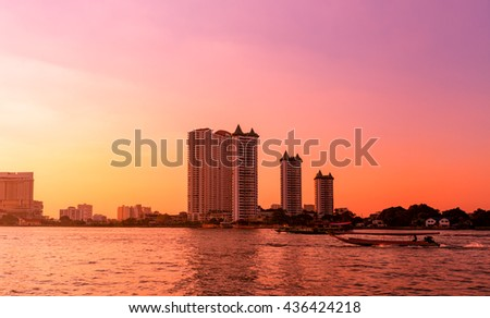 Dramatic sunset on river with building and boat in Chaophraya river, Bangkok, Thailand - stock photo