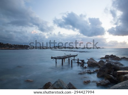 Dramatic sunset on the Mediterranean Sea, the pier was destroyed by storms - stock photo