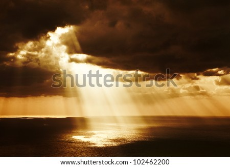 Dramatic sunset on the sea, beautiful peaceful scene, bright sun light, rays of light shine in water, sunbeam in cloudy sky, summer ocean view, paradise beach - stock photo