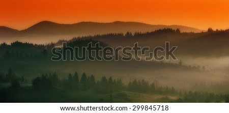 Dramatic sunset on the slopes fog midst of trees - stock photo